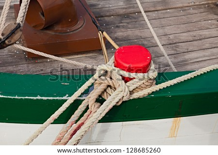 rope of boat knotting in harbor - ropes around a pole for mooring an old wooden vessel - ship hemp cable bound over a bollard - stock photo