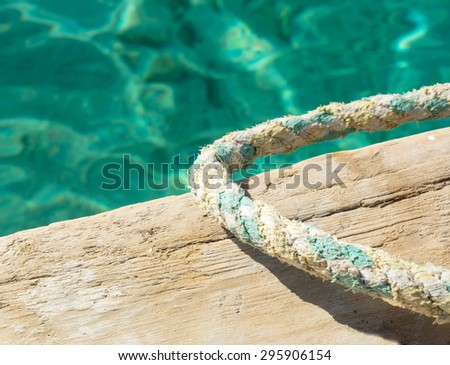 rope of the pier on the background of emerald sea - stock photo