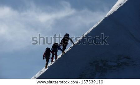 Rope team climbing icy mountain ridge - stock photo