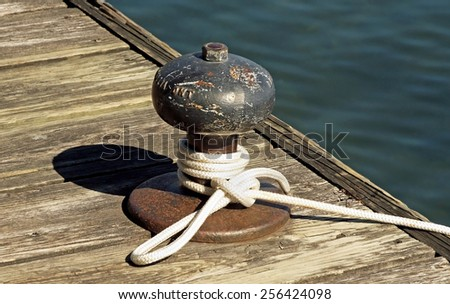 Rope tied to a metal boat slip at dock - stock photo