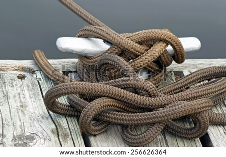 Rope tied to metal slip on boating dock - stock photo