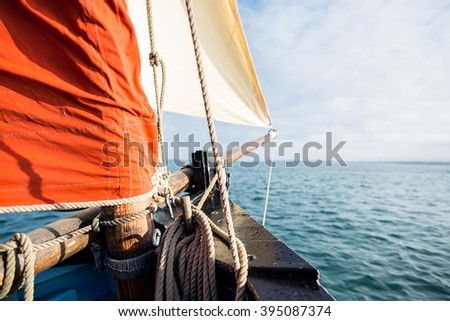 rope wound on a wooden cleat fixed on the hull of a rigging vintage sailing boat with a beige jib and an ocher sail filled by the wind at the blur background during a sunny sea trip in brittany