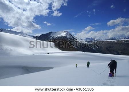 Roped mountaineering team in snowshoes trying to avoid crevasses and reach the pass. - stock photo