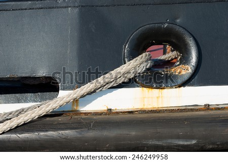 Ropes Tying a Ship to the Dock in Port. Detail of the ropes of a black tugboat with rust - stock photo