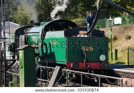 ROPLEY, UK - 19 SEPTEMBER: An engineer filling the water tender of a vintage steam locomotive at the Mid-Hants Watercress railway station of Ropley, UK on 19 September, 2015 - stock photo