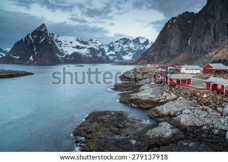 Rorbu cottages with mountains in background, Lofoten islands, Norway - stock photo