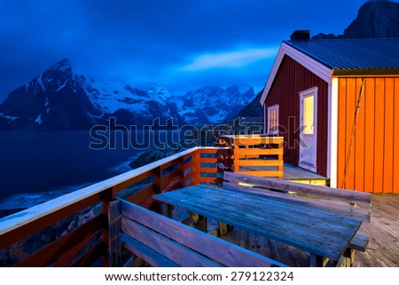 Rorbu - typical wooden cottage of fishermen and Olstind mountain peak in background, Hamnoy village, Lofoten islands, Norway - stock photo