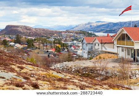 Rorvik. Fishing Norwegian town with colorful wooden houses on rocky hills - stock photo