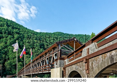 Rosa Khutor, Sochi, Russia - July 09, 2015: Wide view of pedestrian bridge over Mzymta river leading from the railway station to the ski resorts of Gazprom and Rosa Khutor.