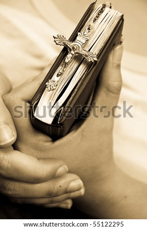 Rosary and Bible Clutched By Female Hands - stock photo