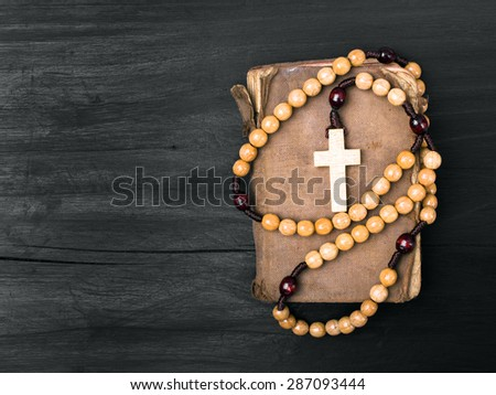 rosary and prayer book on a dark background - stock photo