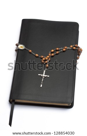 Rosary beads wrapped around the bible on white background - stock photo