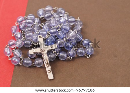 Rosary Cross with Prayer Beads on Bible - stock photo