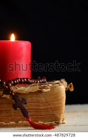 Rosary with a cross, old Bible and a candle