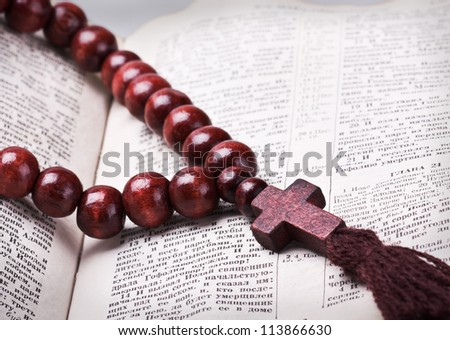 rosary with a wooden cross lying on open Bible - stock photo