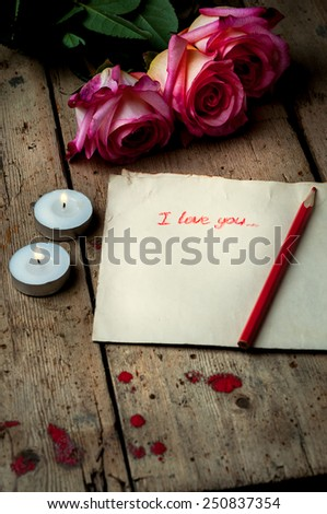 "Rose and a note with the text ""I love you"" on a wooden background.Two small candles. - stock photo"