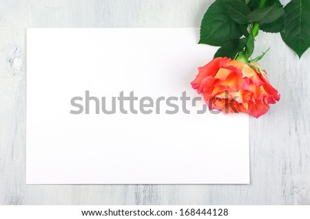 Rose and blank sheet on vintage wooden table.