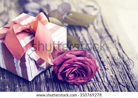 Rose and present gift on wooden background/ Valentines day background - stock photo