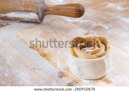 Rose apples and dough. Homemade cakes on a light wooden table with flour. - stock photo