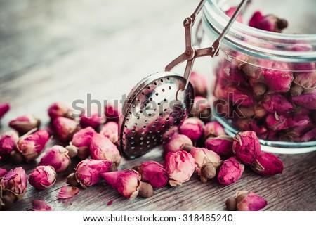 Rose buds tea, tea strainer and glass jar. Selective focus. - stock photo