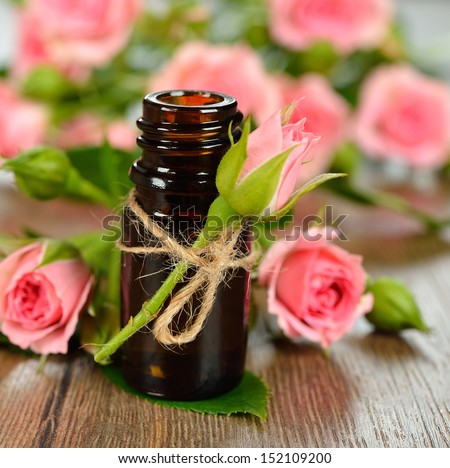 Rose essential oil close-up on a brown background - stock photo