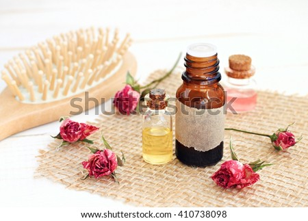 Rose essential oil, rose water, hair brush. Aromatic herbal essences hair care.  - stock photo