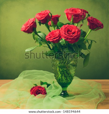 Rose flower bouquet in green glass retro vase over grunge background - stock photo