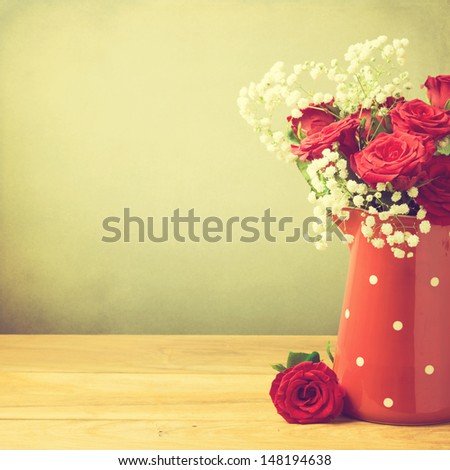 Rose flower bouquet in red polka dots jug with copy space - stock photo