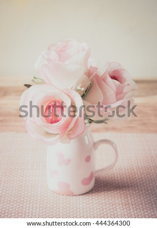 Rose flower of vase on wood table made vintage style