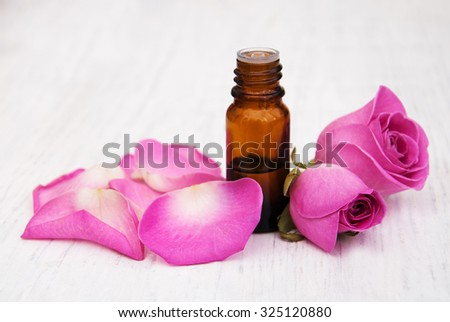 rose flower petals and buds with aromatherapy essential oil glass bottle