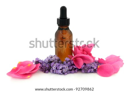 Rose flower petals and lavender herb flowers with aromatherapy brown glass dropper bottle isolated over white background. Lavandula and rosa rugosa. - stock photo