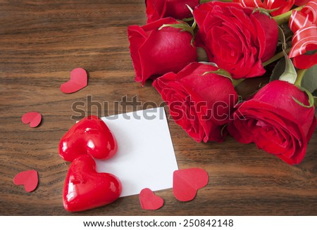 Rose flowers and heart symbol bunch on wooden desk with white blank. Valentine's day concept. Love concept - stock photo