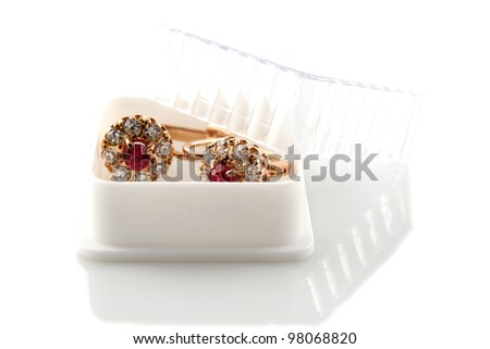 Rose gold earrings with ruby and diamonds in a gift box - stock photo