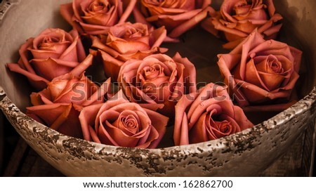 Rose heads floating in grungy ceramic bowl standing on wooden surface. - stock photo