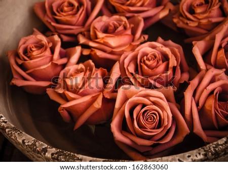 Rose heads floating in grungy ceramic bowl standing on wooden surface. Selective focus on the closest rose. Retro style greeting card. - stock photo