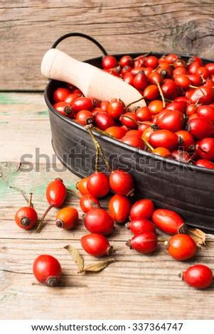 Rose hip in a metal tray on a wooden background
