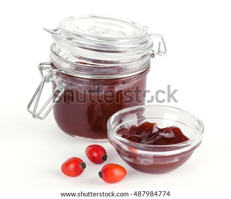 Rose hip jam and fruits over white, also rose haw or rose hep. Marmalade in a glass jar and bowl. Shells of red ripe fruits can be eaten raw and are one of the richest vitamin C sources in plants.