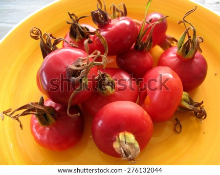 Rose hips on yellow plate - stock photo