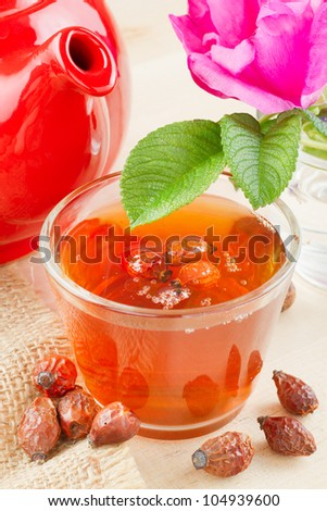 rose hips tea, red teapot and rose-hip flowers - stock photo