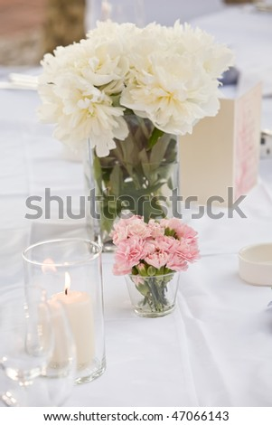 Rose in a vase on a table with a candle - stock photo
