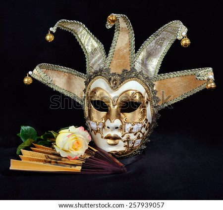 Rose mask and a fan on a black background