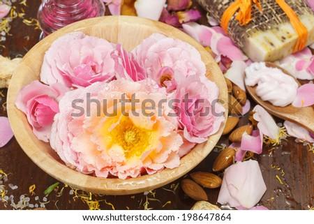Rose petal bath. Spa setting with flowers, sea salt and essential oil. Spa theme. - stock photo