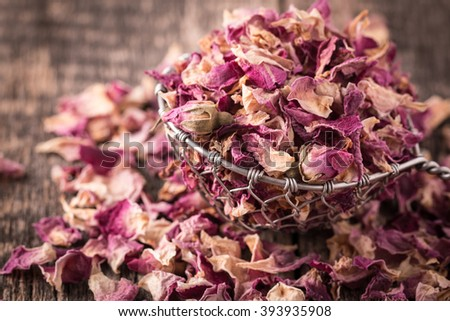 rose petals and dried flowers in spoon on old wooden table - stock photo