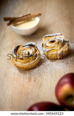 rose-shaped baked pastry with powdered sugar on the move, vanilla cinnamon apple background