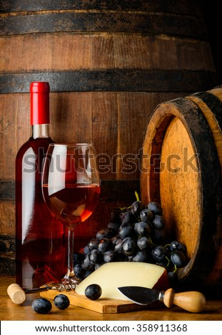 Rose wine bootle and glass, cheese and grapes in still life on wooden barrel background