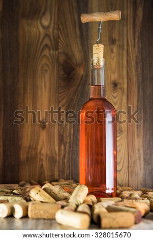Rose wine in a transparent bottle, cork and a corkscrew on the background boards