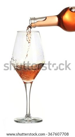 Rose wine pouring in glass, isolated on white