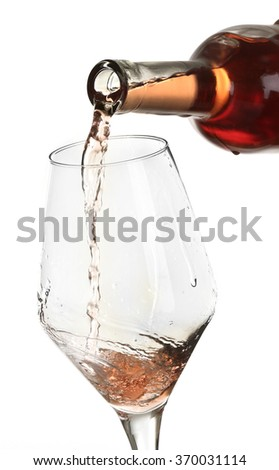 Rose wine pouring in glass, isolated on white - stock photo