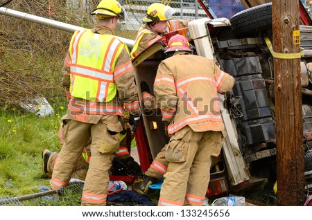 ROSEBURG, OR - MARCH 2013: Emergency workers at the scene of a single car, rollover accident during a spring rain in Roseburg Oregon, March 19, 2013