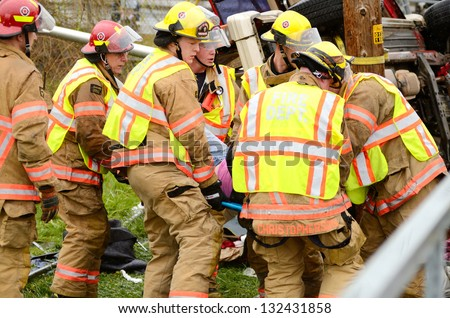 ROSEBURG, OR - MARCH 19: Emergency workers extricate a victim from a single car, rollover accident during a spring rain in Roseburg Oregon, March 19, 2013